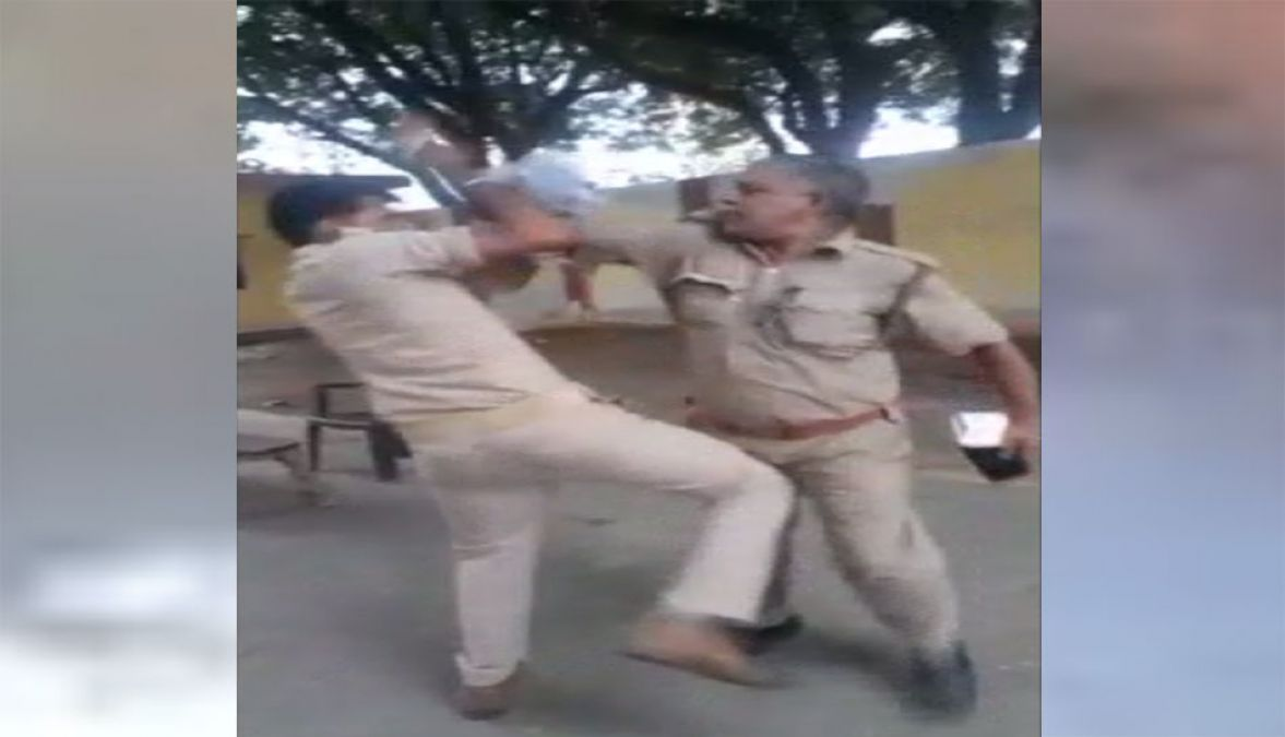 Two policemen fight with each other on mid-road for