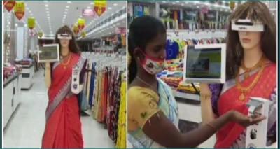 This robot walks around wearing a sari in the shop, her work is praiseworthy